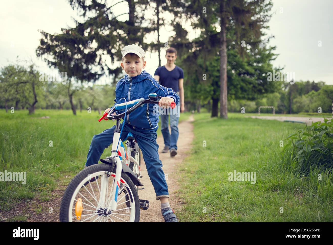 Kleiner Junge mit dem Fahrrad gemeinsam mit seinem Vater. Junger Mann Lehren seines Sohnes, mit dem Fahrrad im freien Stockbild
