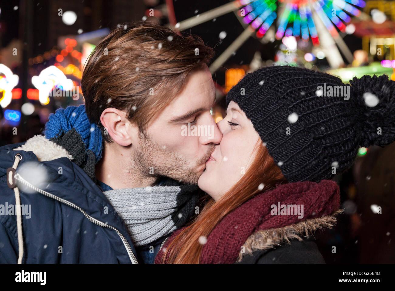 Paar am Weihnachtsmarkt mit Schneeflocken Stockfoto