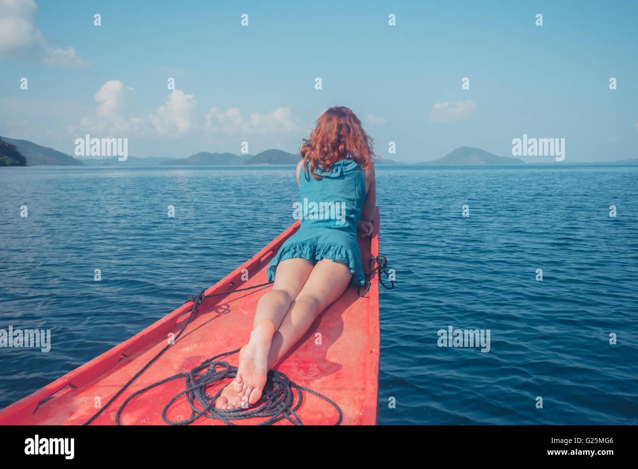Eine junge Frau ist entspannend auf dem Bug eines kleinen Bootes in einem tropischen Klima Stockbild