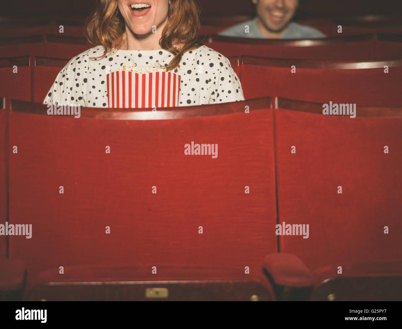 Ein paar Leute sind gerade einen Film in einem Kino Stockbild