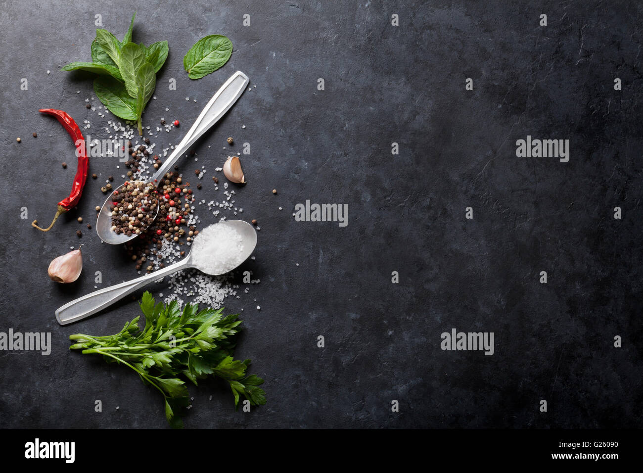 Schwarzen, weißen und roten Pfeffer und Salz Gewürze in Löffel. Minze und Petersilie Kräuter. Stockbild
