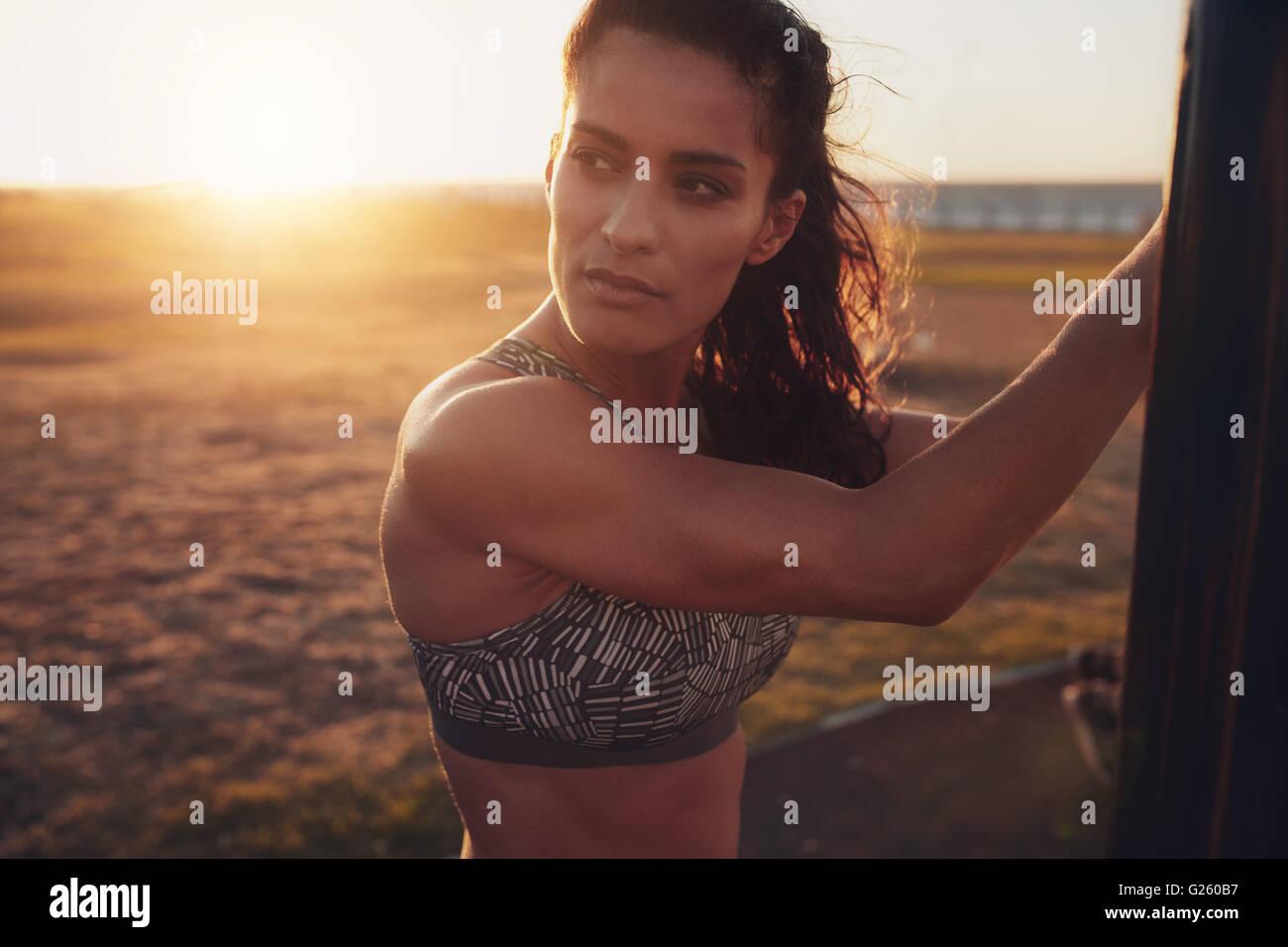 Schuss von Fit junge Frau im Sport BH wegsehen hautnah. Nachdenklich Fitness Frauen stehen im Freien an einem sonnigen Stockbild
