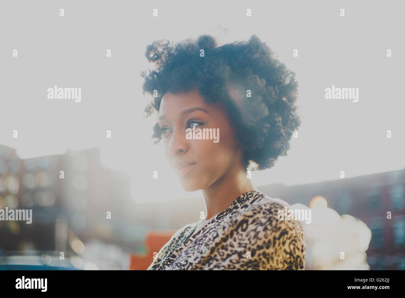Junge Frau mit Afro lächelnd im städtischen Umfeld Stockbild