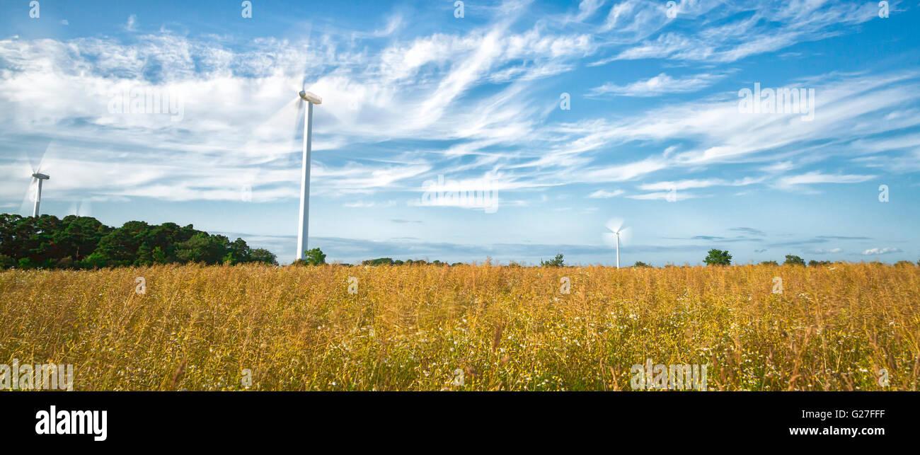 Windkraftanlagen im Feld mit einem teilweise bewölkten Himmel Stockbild