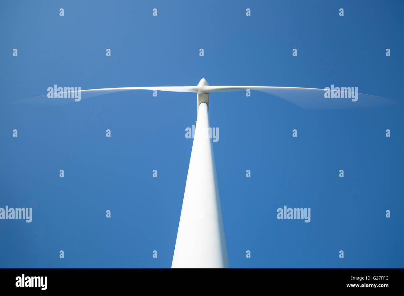 Wind-Kraftwerk von unten mit einem klaren blauen Himmel dahinter Stockbild
