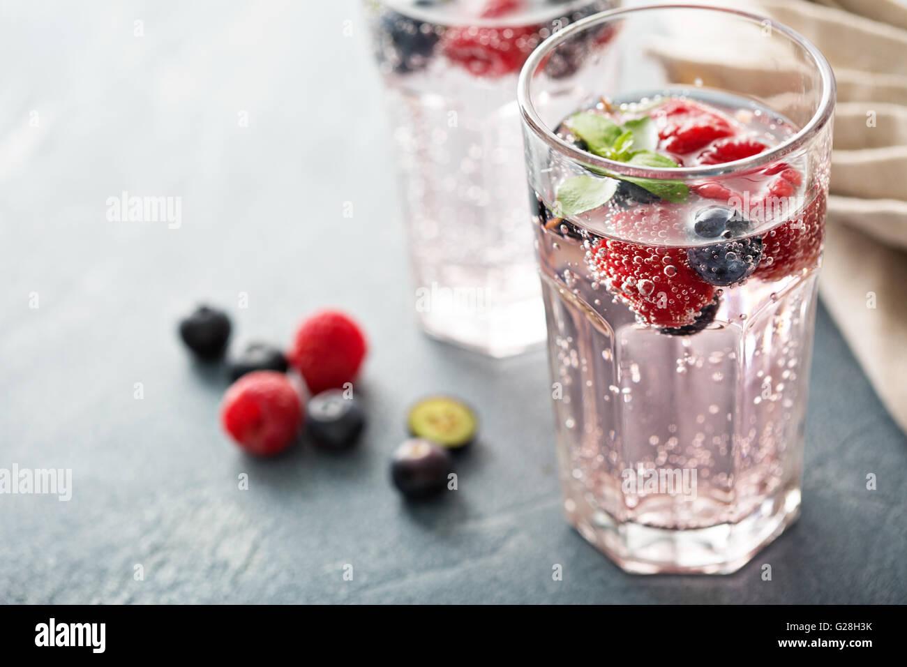 Mineralwasser mit Himbeeren und Heidelbeeren Stockbild
