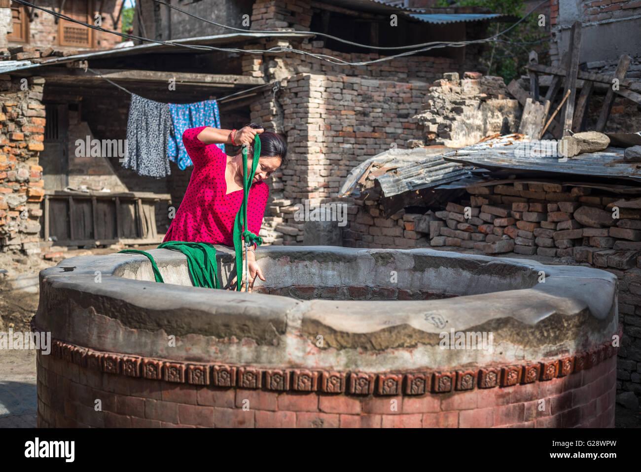 Eine Frau zeichnen Wasser aus einem Brunnen im alten Viertel von Bhaktapur, Nepal. © Reynold Sumayku Stockbild