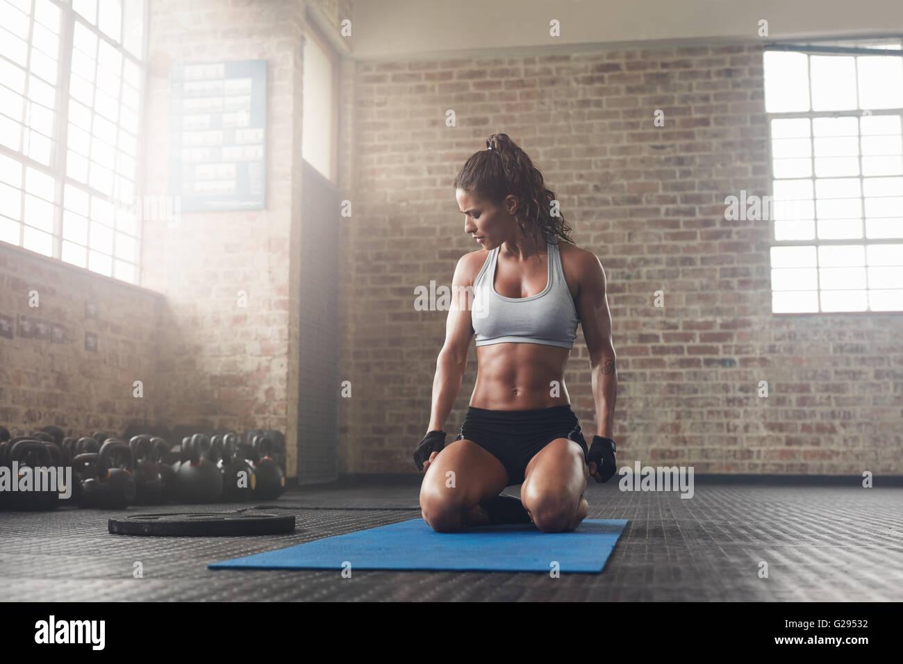 Innenaufnahme des Fitness junge Frau sitzt auf Yoga-Matte im Fitnessstudio. Muskulöse junge Sportlerin eine Stockbild
