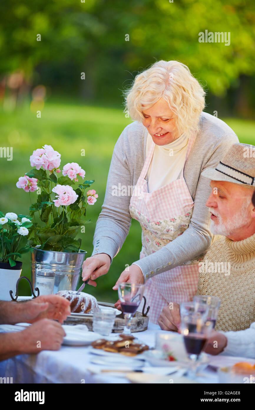 Ältere Frau Guglhupf auf Geburtstagsparty in einem Garten Stockbild
