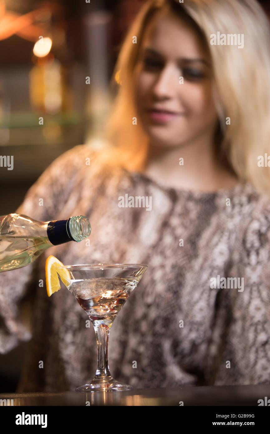 Lächelnden blonden weiblichen Barkeeper Vorbereitung Alkohol Getränk an der Theke, halten Sie die Flasche Stockbild