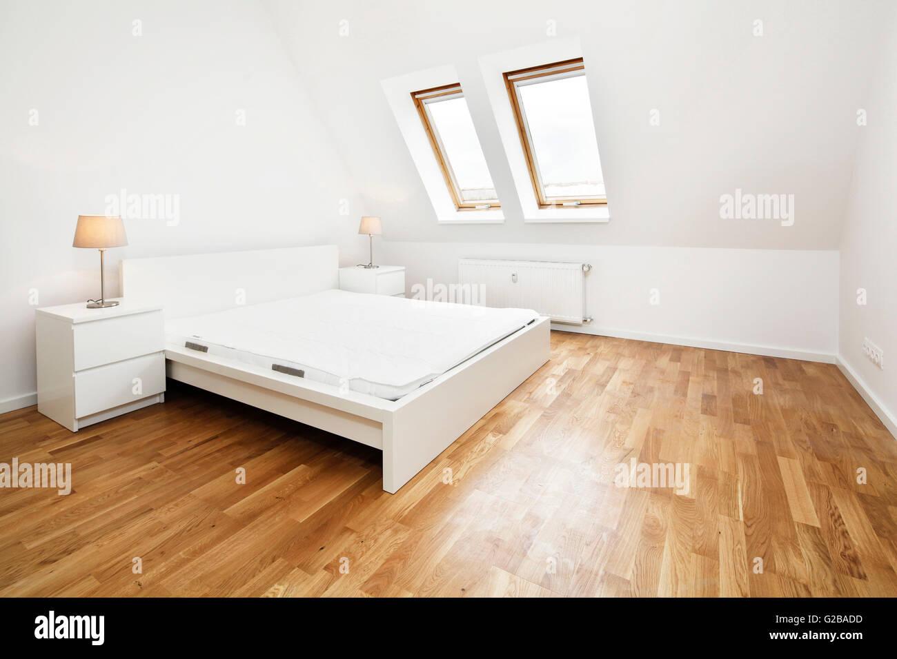 Moderne Schlafzimmer Mit Schrägen Wänden. Weiße Wände Und Holzböden Mit  Minimalen Möbeln Und Dekoration.
