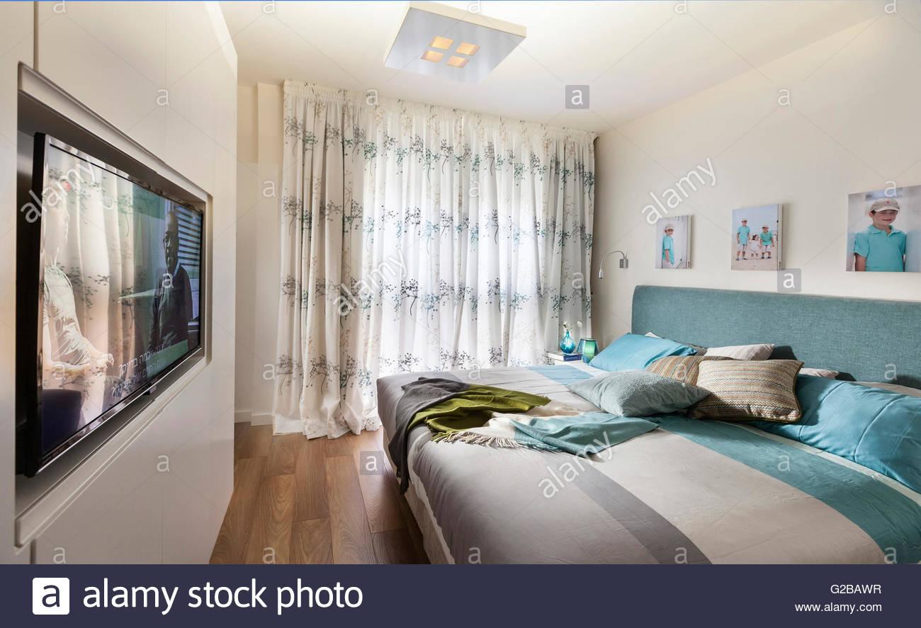 Modern, Minimalistisch Eingerichtete Schlafzimmer. Großes Bett Mit Einem  Flachbildschirm Fernseher An Der Wand.