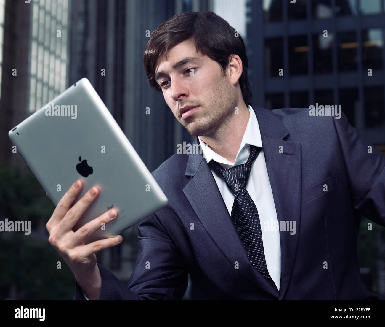 Geschäftsmann im Anzug mit Apple iPad Tablet-Computer mit Innenstadtbüro Gebäude am Rücken, Stockbild