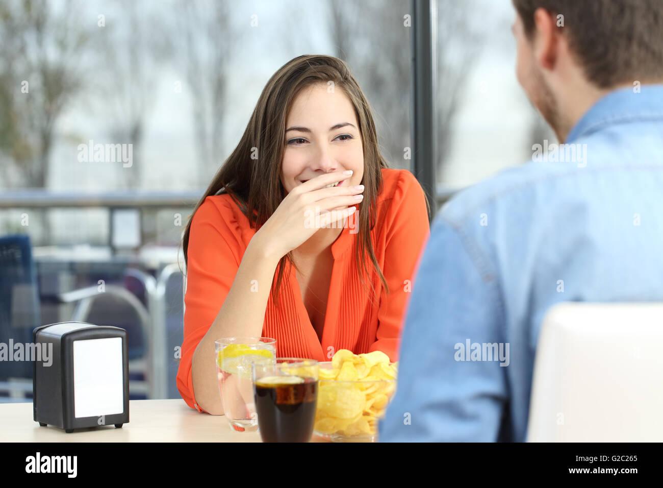 Frau, die ihr den Mund zu Lächeln oder Mundgeruch während ein Datum in einem Café mit einem Fenster Stockbild