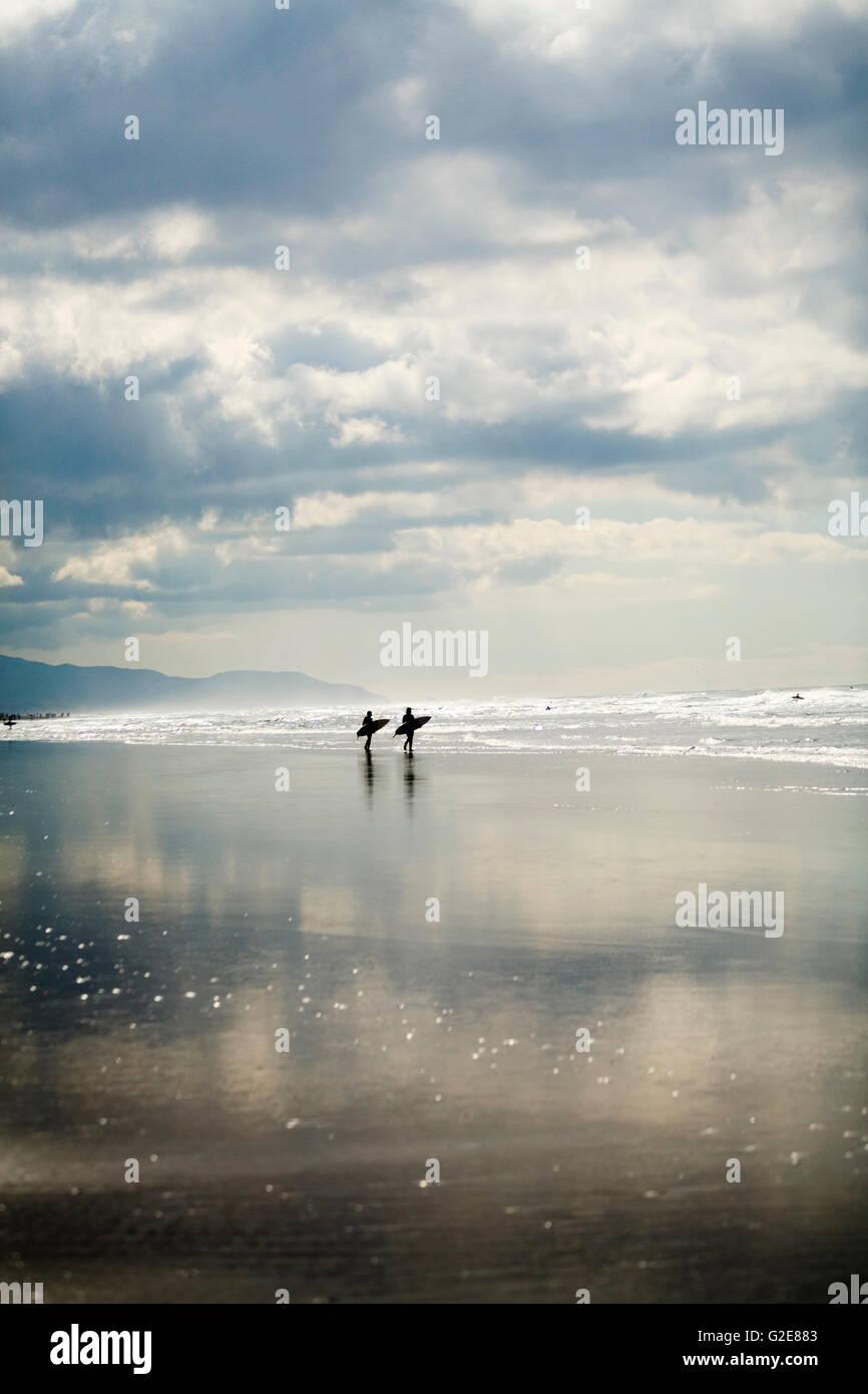Zwei Surfer zu Fuß am Strand Stockfoto