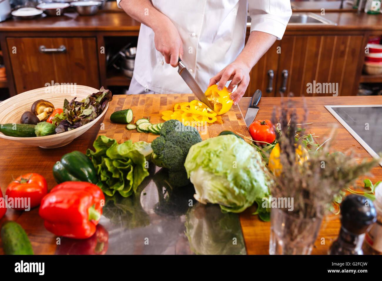 Nahaufnahme von Chef-Koch stehen und machen Salat auf dem Küchentisch Stockbild