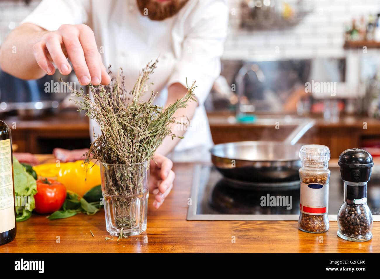 Abgeschnitten Bild ein Chef Koch bereitet Lebensmittel in der Küche Stockbild