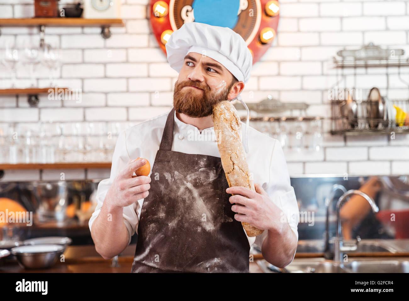 Nachdenklich bärtigen Bäcker holding, Eiern und Brot und denken auf ...