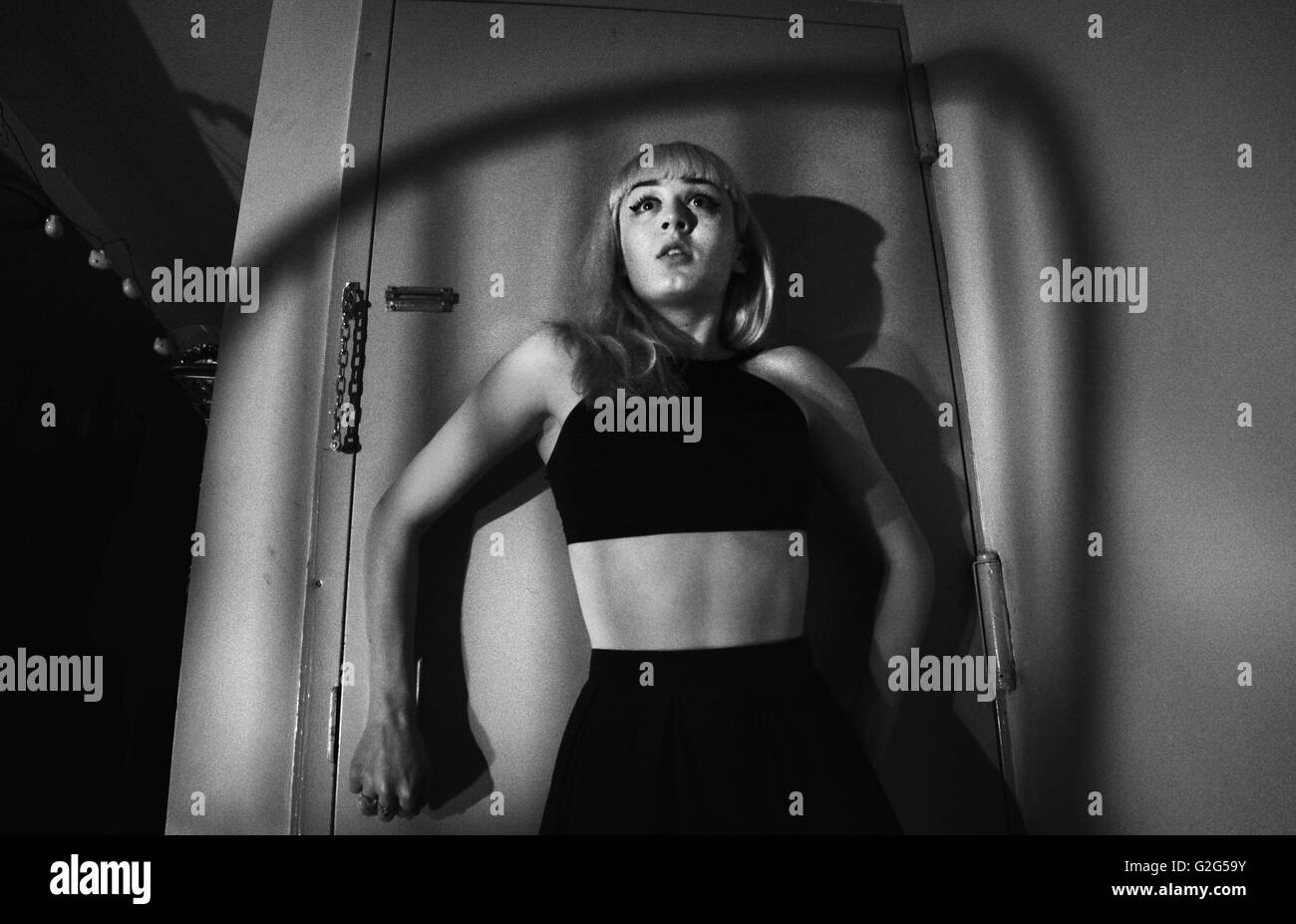 Verängstigte junge Frau gegen Tür mit überlappenden Schatten der Stuhl Stockfoto