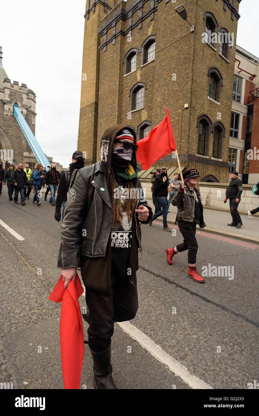 May Day anarchistische Gruppe, mit versteckten Gesichtern, Parolen und roten Fahnen zu Fuß über die Tower Bridge 1. Mai 2016 Stockfoto