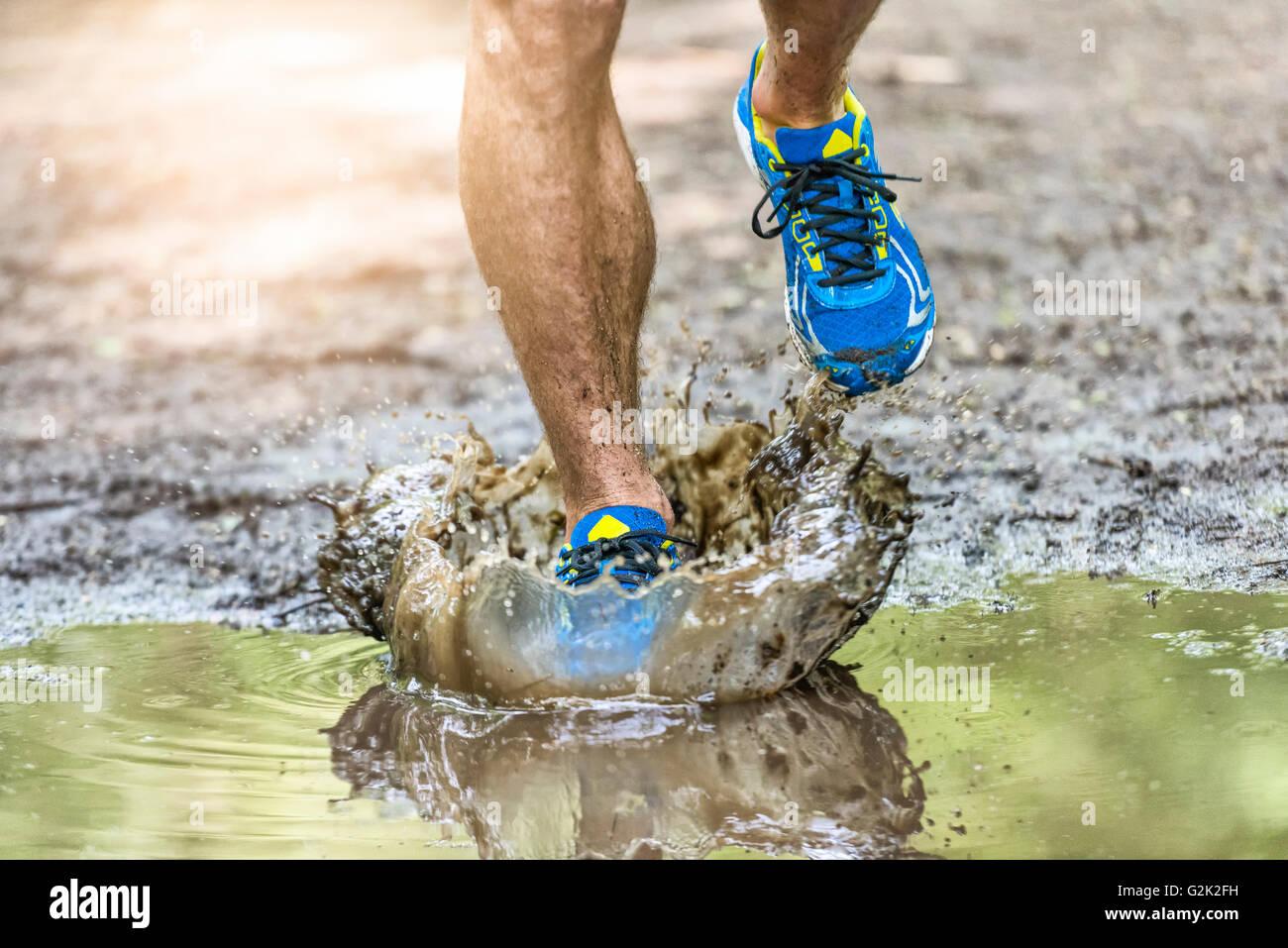 Mann geht in eine Pfütze planschen seine Schuhe läuft. Cross Country Trail. Frieren Aktion ein Stockbild