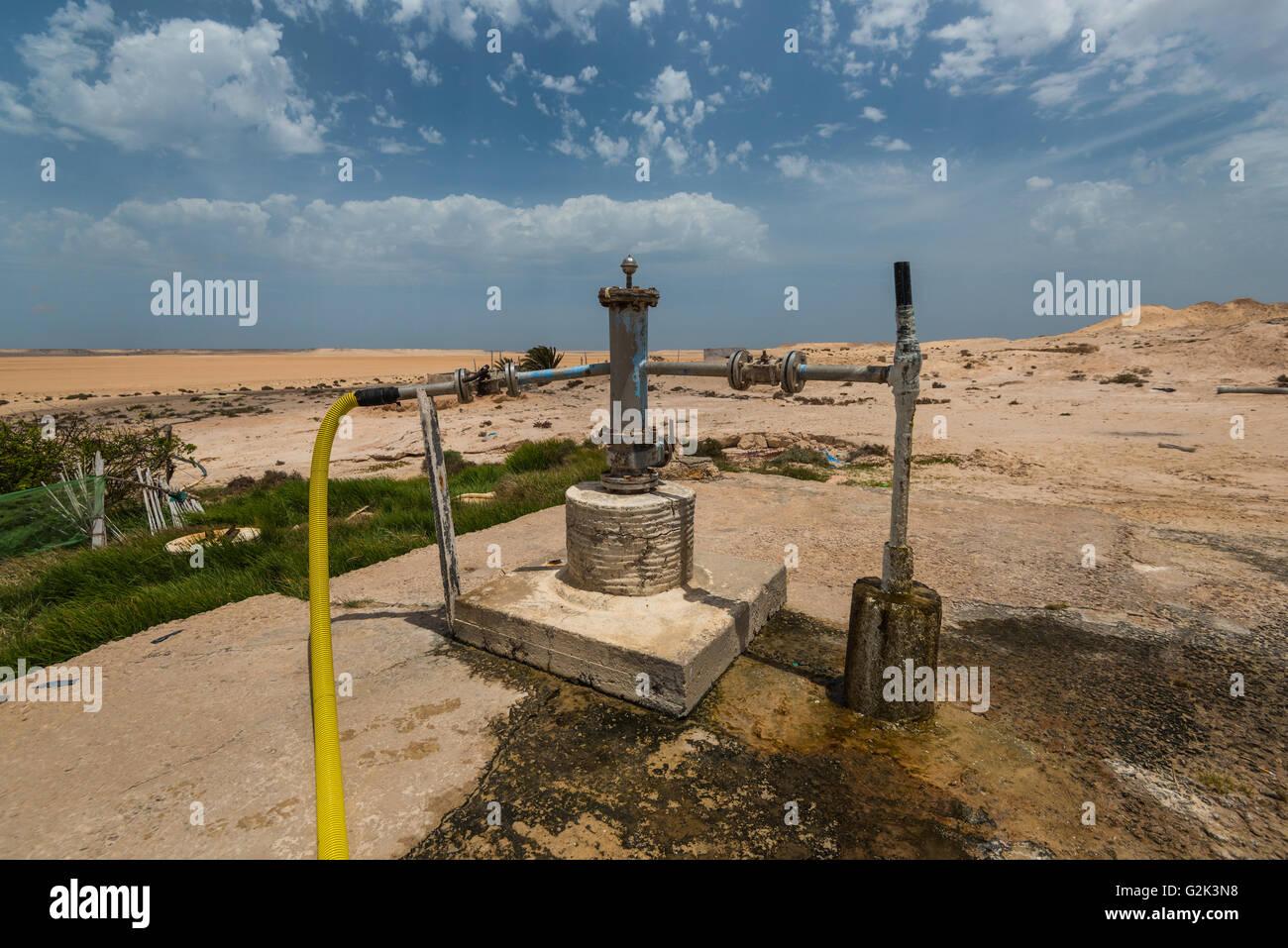 Wasser gut in Sandwüste mit blauen Wolkenhimmel Stockbild