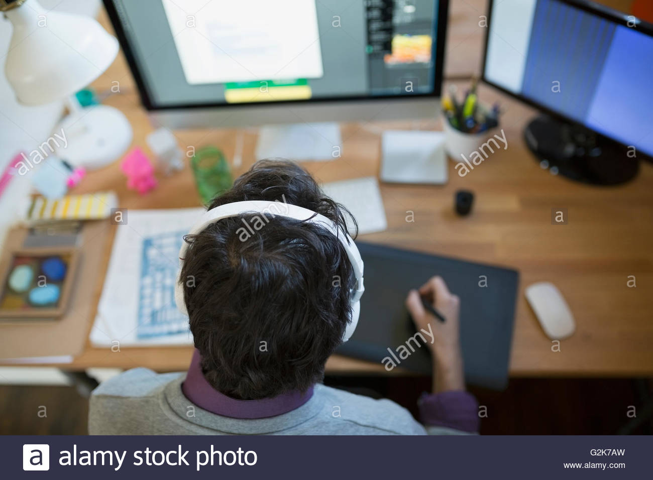 Designer mit Kopfhörern mit Grafiktablett am computer Stockbild