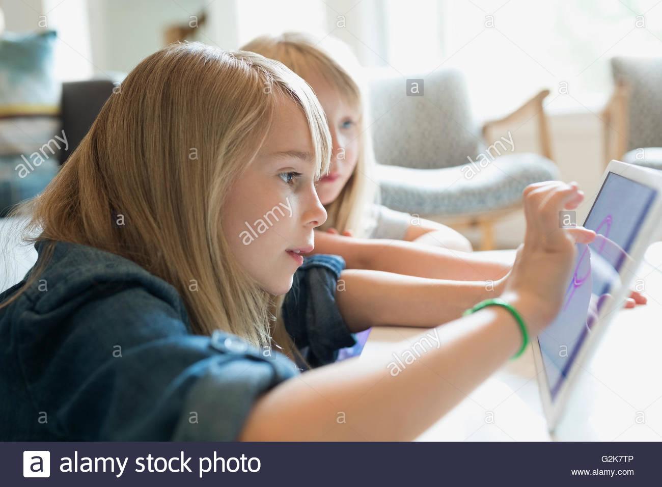 Schwestern, die Zeichnung mit digital-Tablette im Wohnzimmer Stockbild