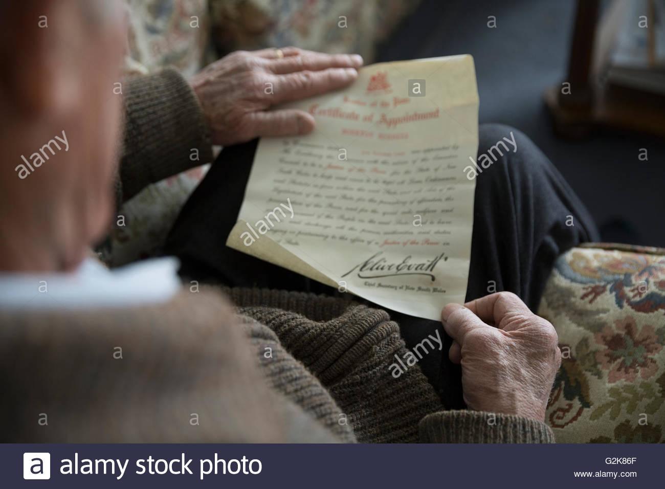 Senior woman lesen altes militärische Zertifikat von Einladungsschreiben Stockbild