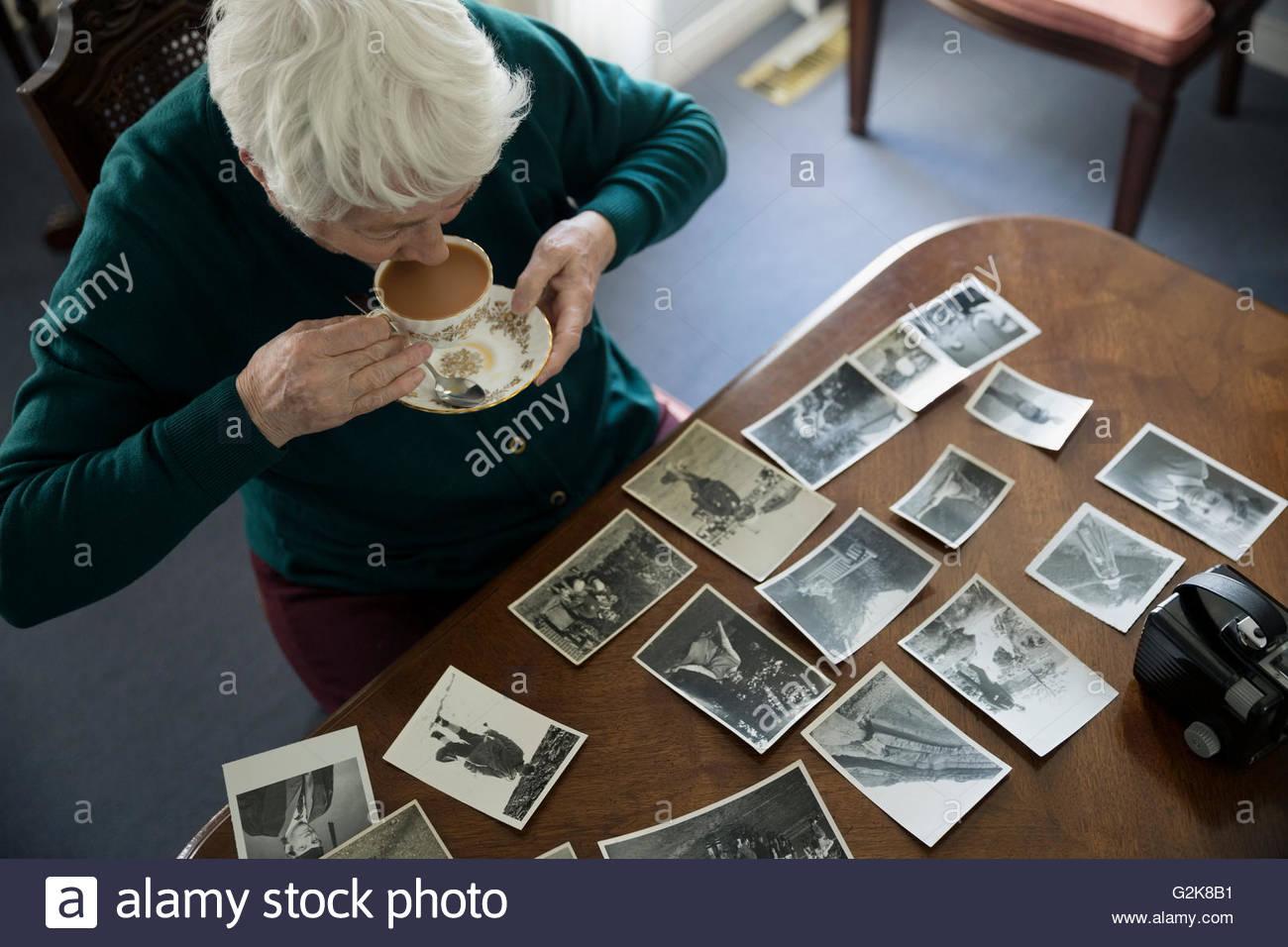 Frauen in Führungspositionen Tee zu trinken und mit Blick auf alten Fotografien Stockbild