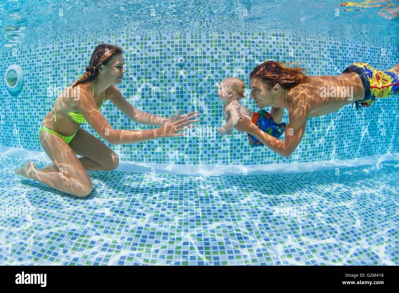 Kind schwimmen Lektion - Baby mit Mutter, Vater lernen, Schwimmen, Tauchen unter Wasser im Schwimmbad. Stockbild
