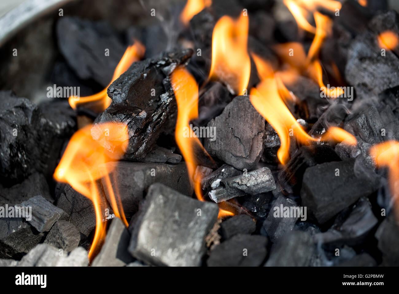 Holzkohle zum Grillen mit leuchtend orangefarbenen Flammen entzünden ...