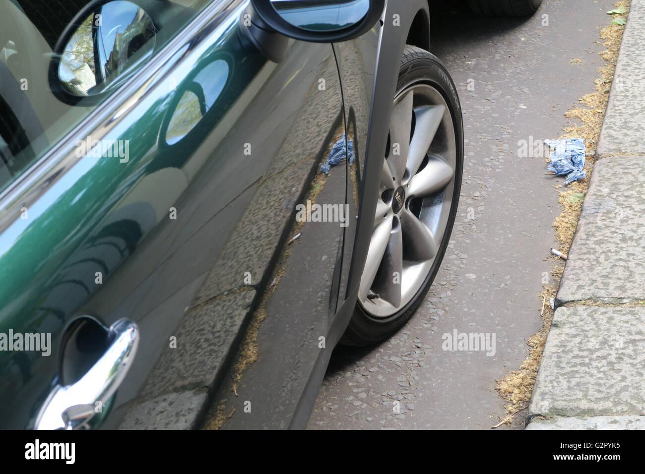 glänzend grünes Auto mit Rad, Pflaster wider Stockbild