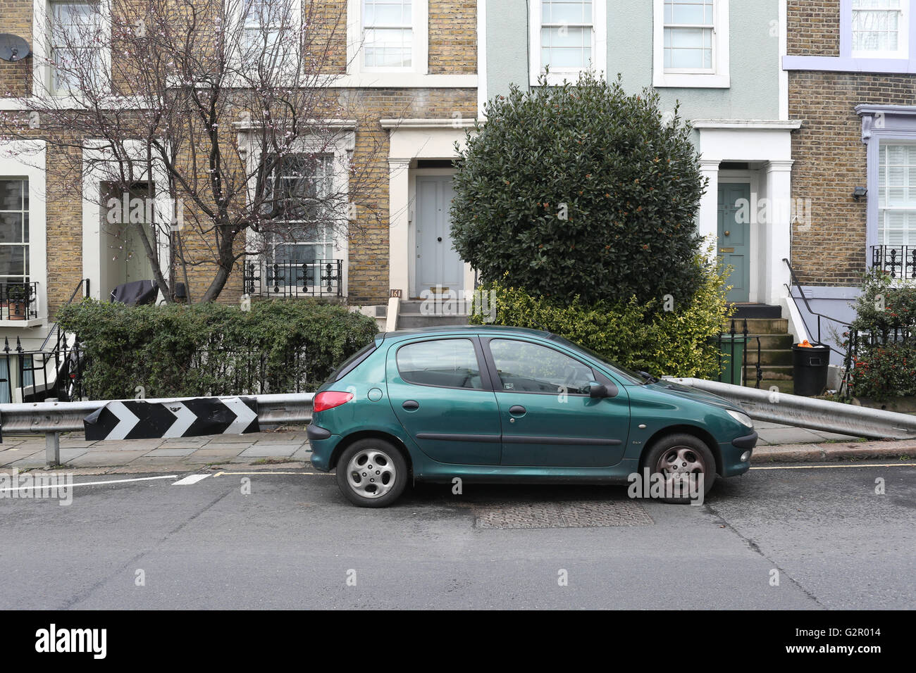 grünes Auto gegen Leitplanke, Häuser Stockbild