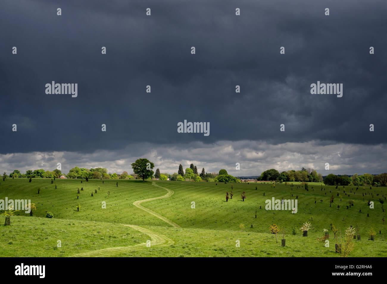 Fußweg beleuchtet gegen einen dunklen Gewitterhimmel durch ein Feld von Oxfordshire. Banbury, Oxfordshire, Stockbild