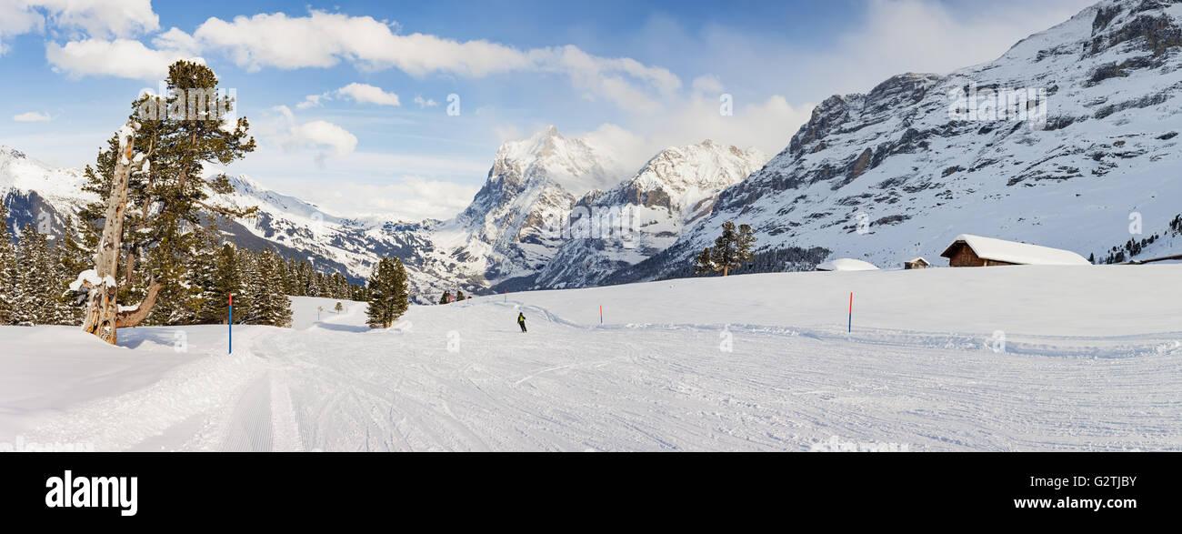 Panoramablick auf einer Skipiste in Grindelwald in der Schweiz mit einem einzigen Skifahrer in der Ferne. Stockbild