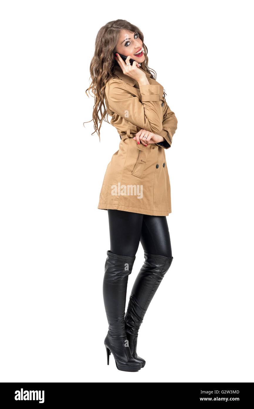 ed9a9405e45 Glücklich lächelnde Frau in Herbst Beige Mantel auf dem Mobiltelefon