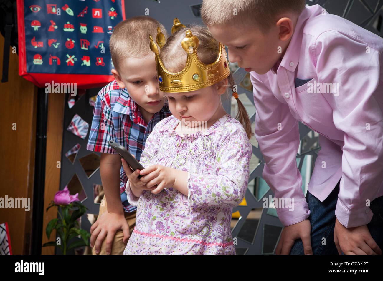 Kinder und sorgfältiger Abwägung der Smartphone Smartphone-Mädchen, das Mädchen mit den jungen Stockbild