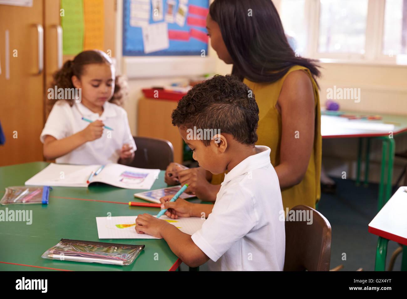 Weibliche Grundschullehrerin helfen Schülern am Schreibtisch Stockfoto
