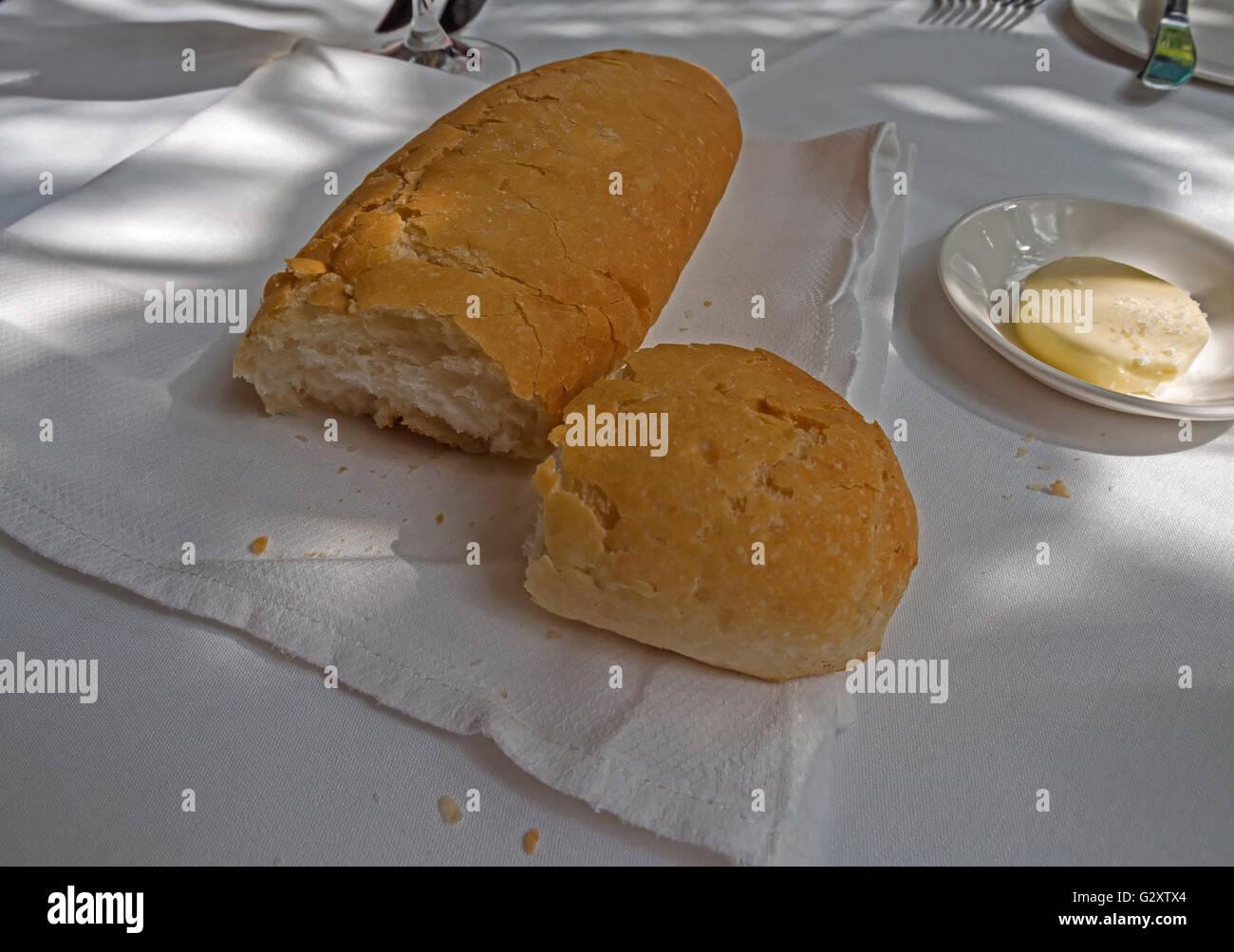 Knuspriges Weißbrot mit einer Schüssel mit Butter auf einer weißen Tischdecke Stockfoto