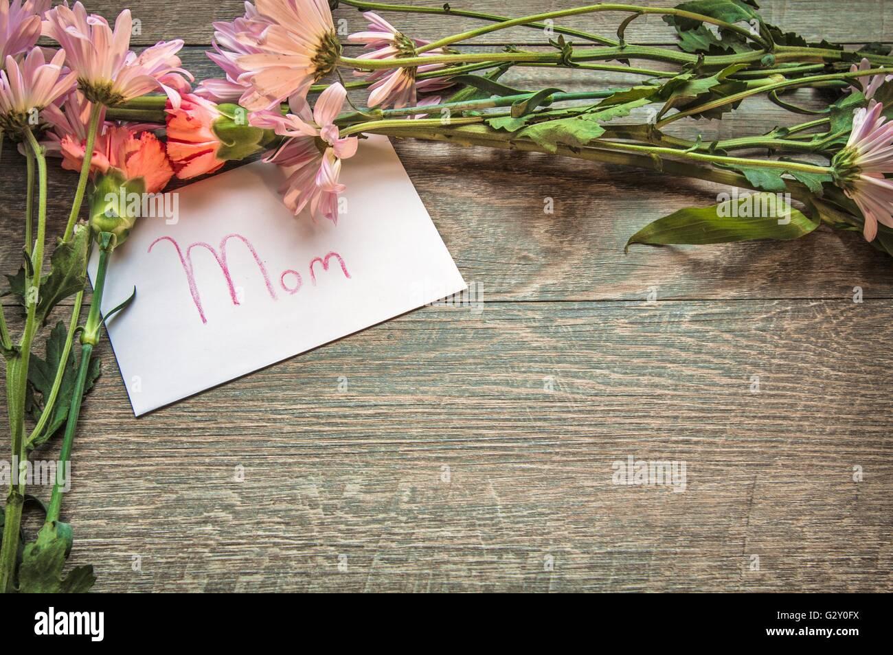 Geschenk für Mama. Blumen umrahmen eine handgeschriebene Karte für ...