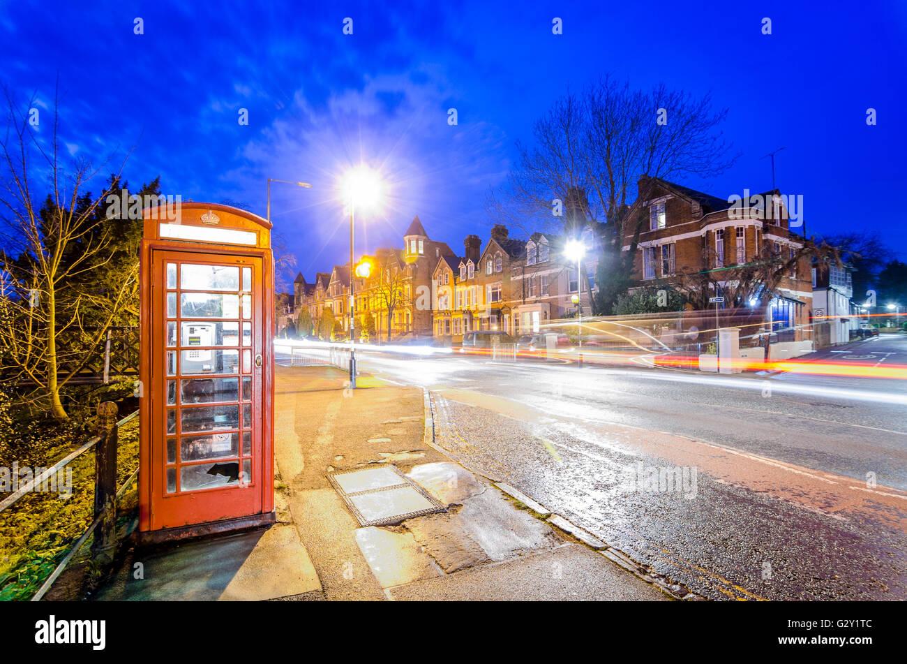 Nacht Szene in Cambridge, Großbritannien, mit roten Telefonzelle und Bewegungsunschärfe leichte Wanderwege Stockbild