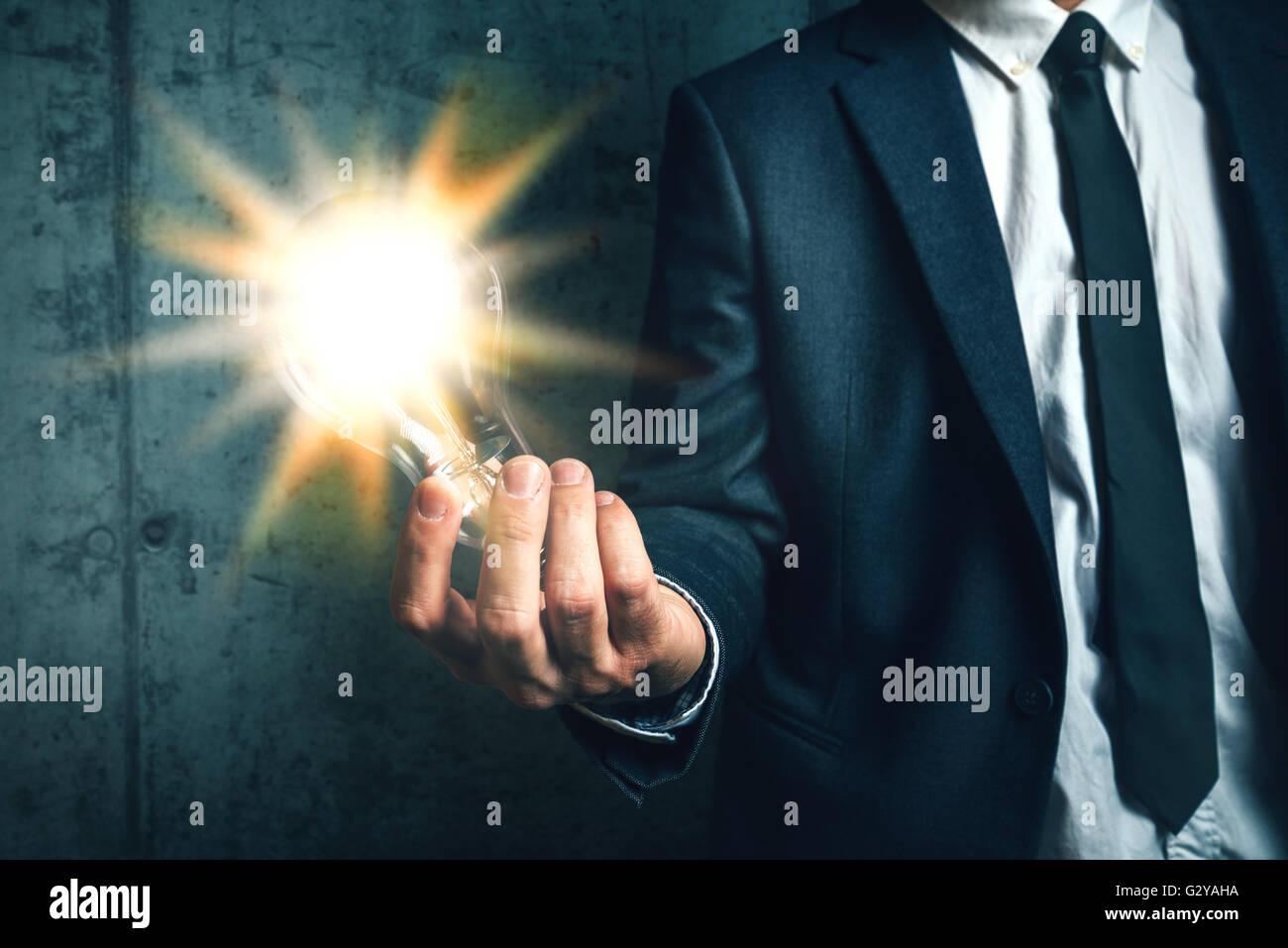 Unternehmen Kreativität und Vision-Konzept mit eleganten Erwachsenen Geschäftsmann hält helle Glühbirne Stockbild