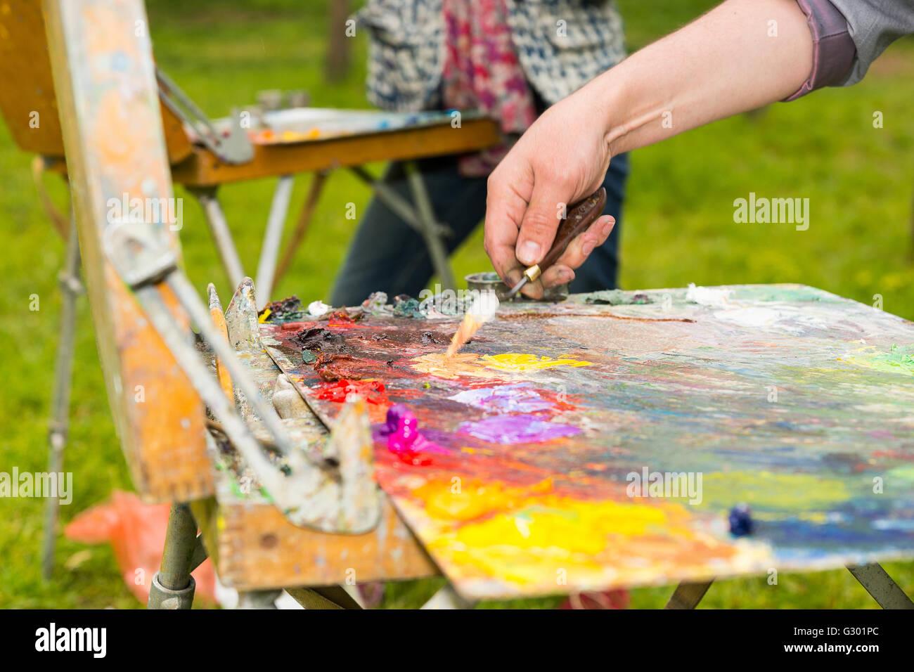 männliche hand mischen lichtfarben von Öl und acryl farbe mit einem