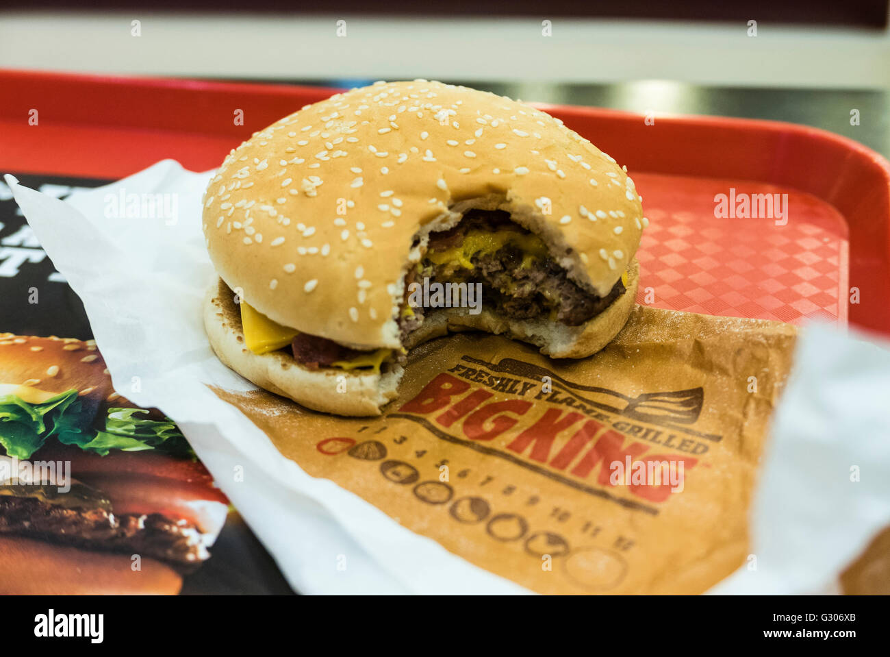 hamburger mit einem biss entnommen auf einem tablett in einem burger king schnellrestaurant. Black Bedroom Furniture Sets. Home Design Ideas