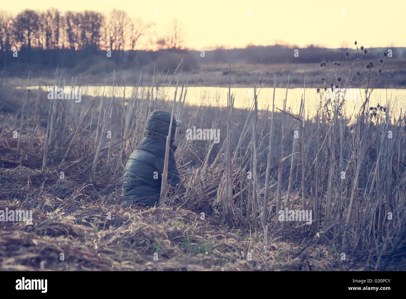Reisende in einem ländlichen Bereich sitzt und die Landschaft genießen. Einsamer Mann wacht über die nebligen Morgen Stockfoto