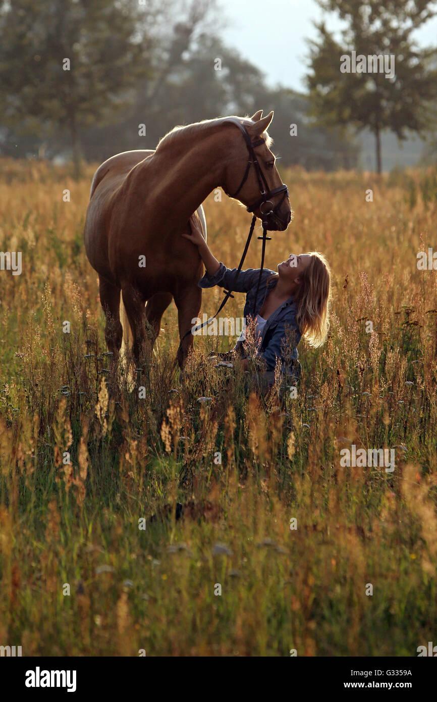 Brieselang, Deutschland, Mädchen kauert auf einer Wiese auf ihr Pferd und betrachtet ihn liebevoll Stockfoto