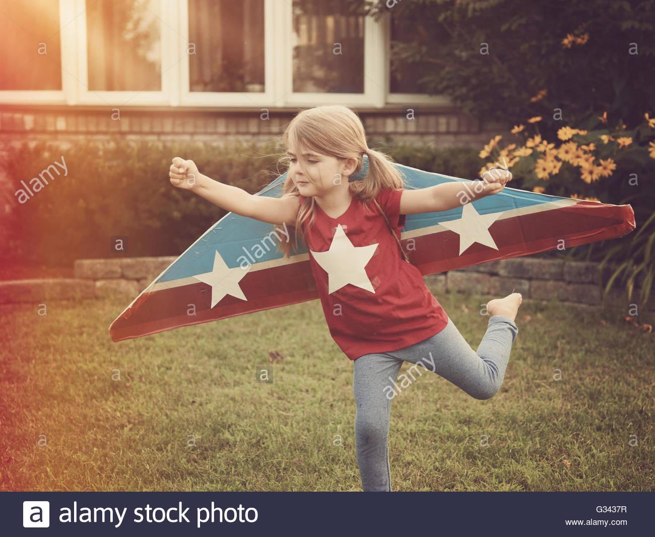 Ein Kind trägt Pappe fliegenden Flügel mit Sternen drauf, die vorgibt, ein Pilotprojekt für ein Handwerk, Stockbild