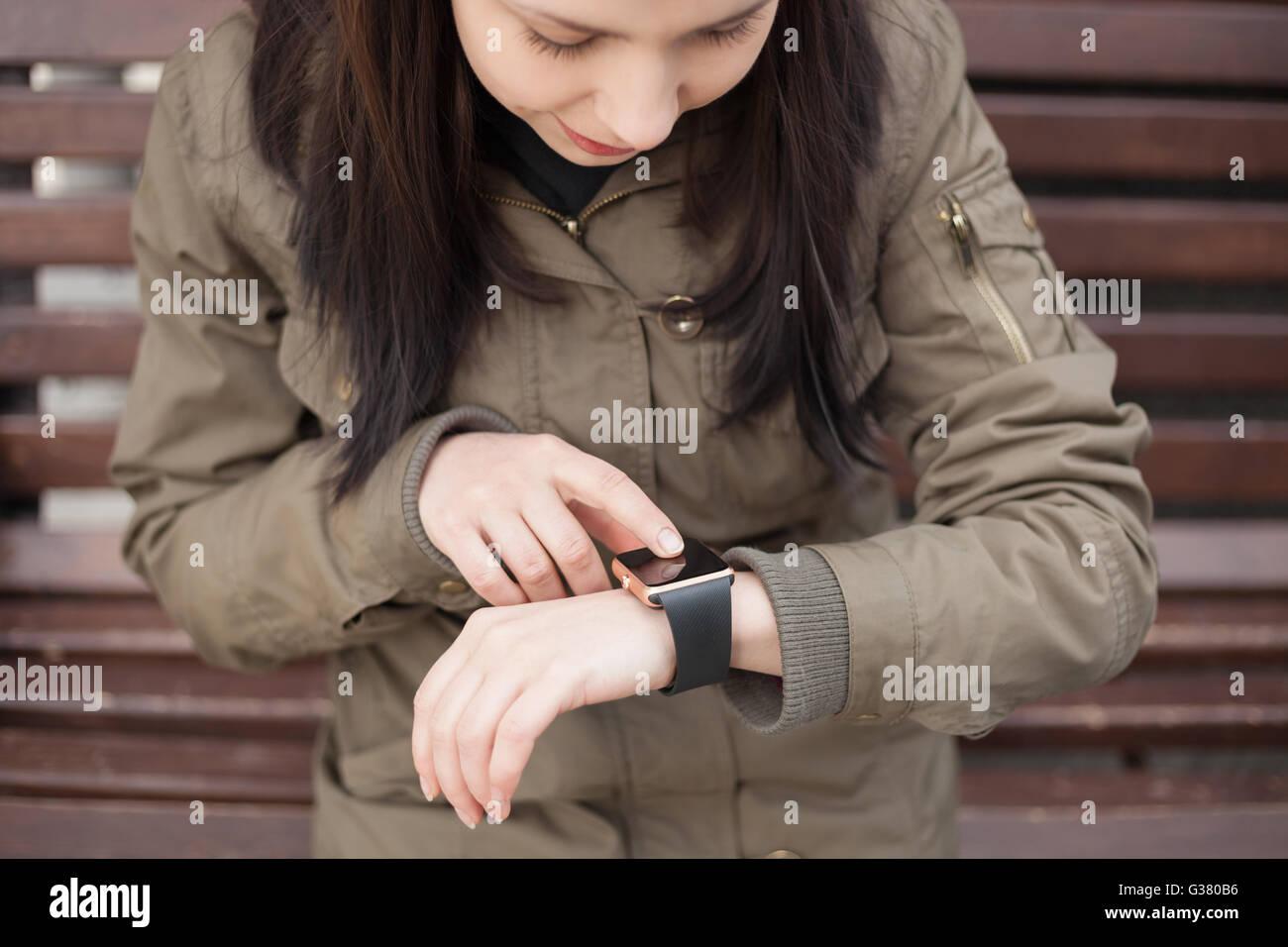 70796d8b90d0 Junge Hipster Mädchen in Parka Mantel mit ihrem smart-Uhr. Das neue Gadget  können