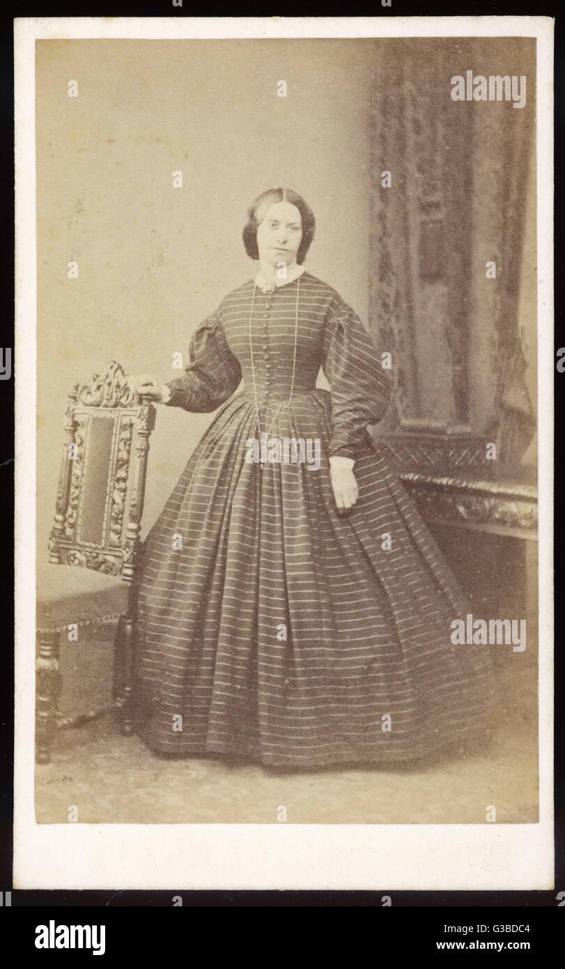 Ein Kleid in einem horizontal gestreiften Stoff mit Front knöpfte Mieder, Gigot Hülsen, weiße Manschetten Stockbild